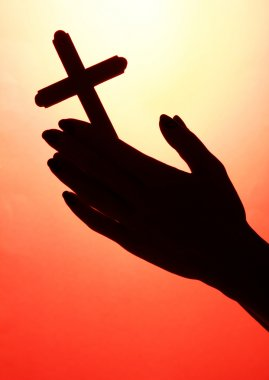 female hands with crucifix, on red background