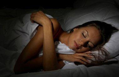 young beautiful woman sleeping in bed in dark bedroom