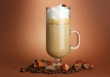 Fragrant coffee latte in glass cup with spices, on brown background