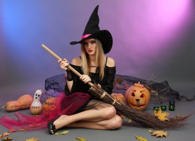 Halloween witch with broom on color background