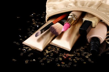 Beautiful golden makeup bag and cosmetics isolated on black
