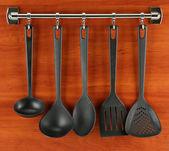 černá kuchyně nádobí na stříbrné háčky, na dřevěné pozadí