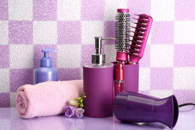 Hair brushes, hairdryer and cosmetic bottles in bathroom