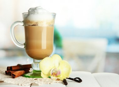 Fragrant coffee latte in glass cup with spices, on wooden table