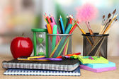 Fotografie School supplies with apple on wooden table