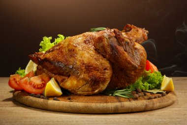 Whole roasted chicken with vegetables, on wooden table, on brown background
