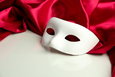 White mask and red silk fabric, isolated on white