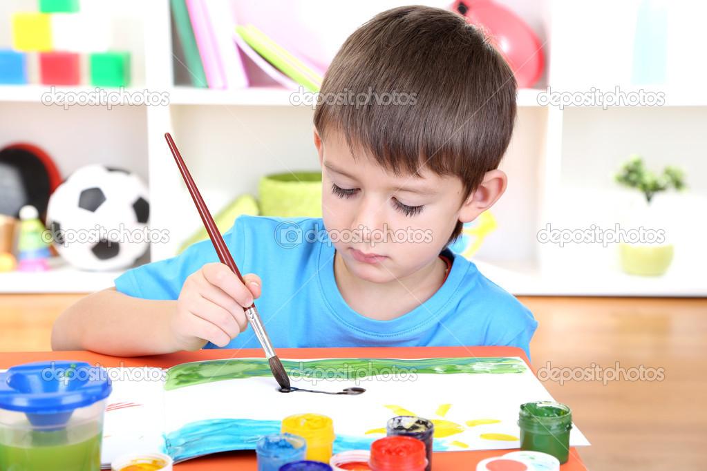 Cute little boy painting in his album — Stock Photo © belchonock #19504085