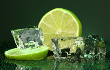 Ice cubes with lime on darck green background