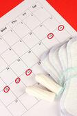 Fotografie Menstruationskalender mit Sanitärpolstern und Tampons, Nahaufnahme