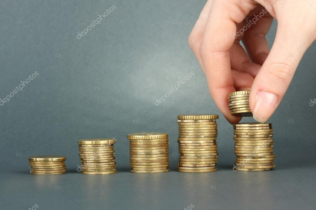 Hand holding coins on grey background