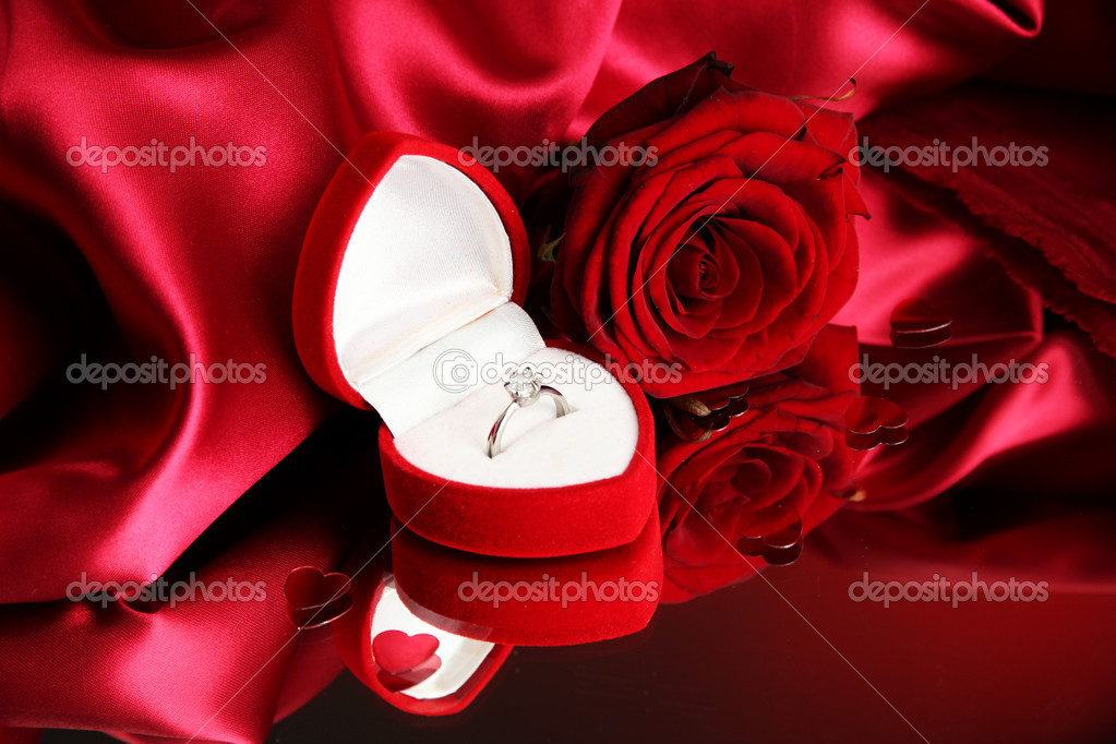 f562bc4f3 Beautiful box with wedding ring and rose on red silk background– stock image