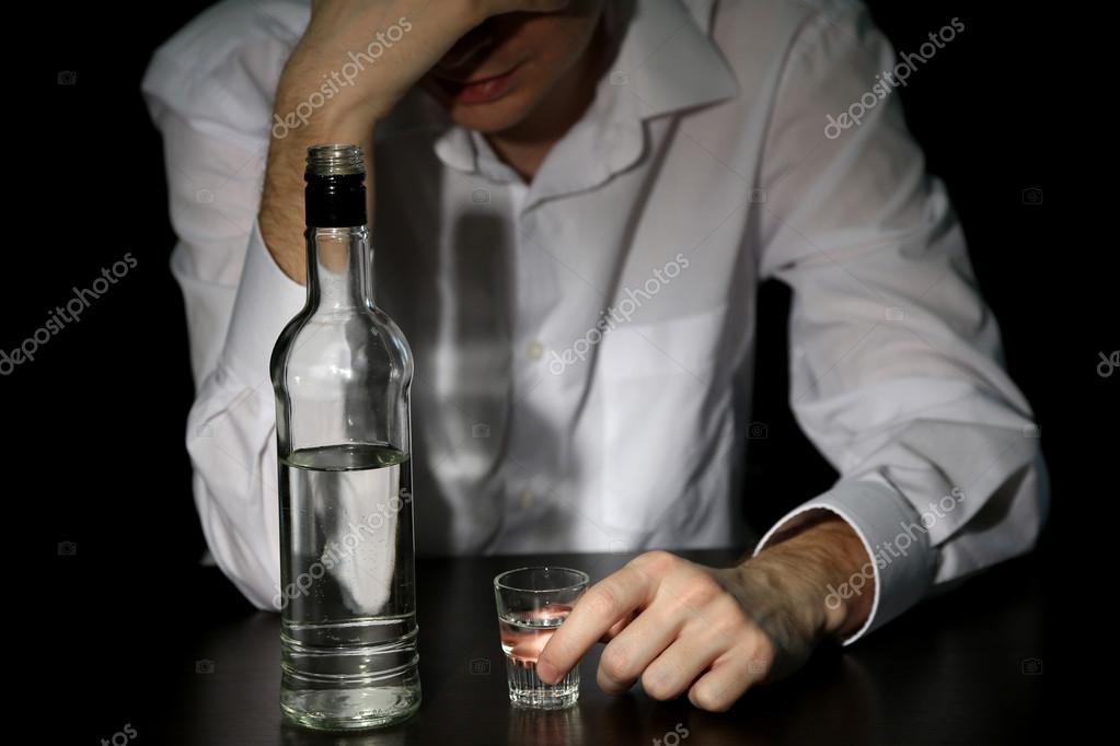 Man with bottle of alcohol, on black background