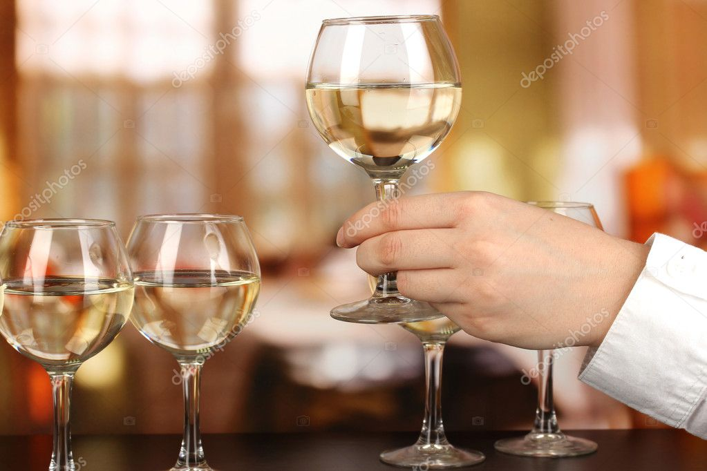 Tasting white wine on room background