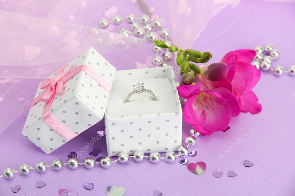 hermosa caja con anillo de bodas y flores sobre fondo púrpura — Foto ...