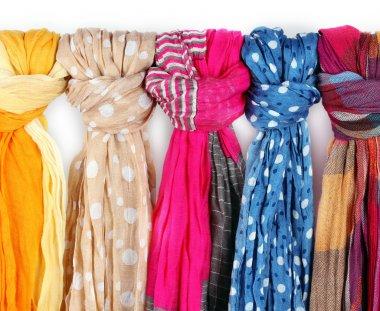 Many bright female scarfs close-up