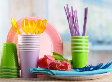 Multicolored plastic tableware on table with tulips close up