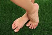 Gyönyörű nő lába a zöld fű