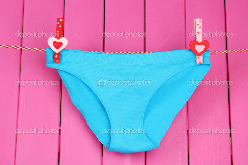 a8e2195fccb2 Womans panties hanging on a clothesline, on pink wooden background — Stock  Photo