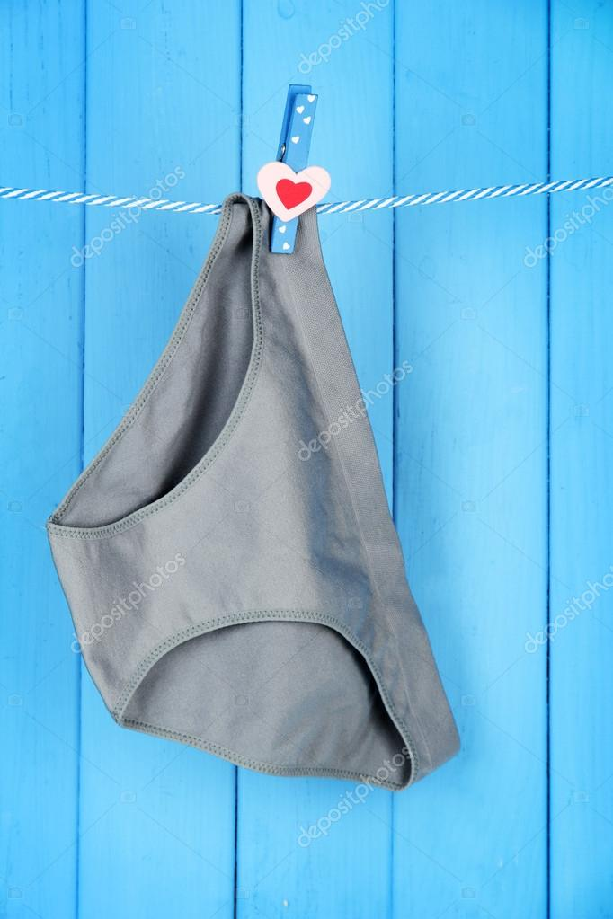 210d784e5b24 Womans panties hanging on a clothesline, on blue wooden background — Stock  Photo