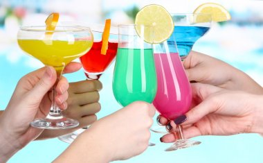 Cocktails in hands on pool background
