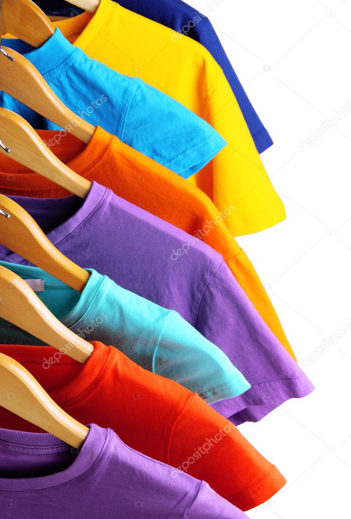 Lots of T-shirts on hangers isolated on white