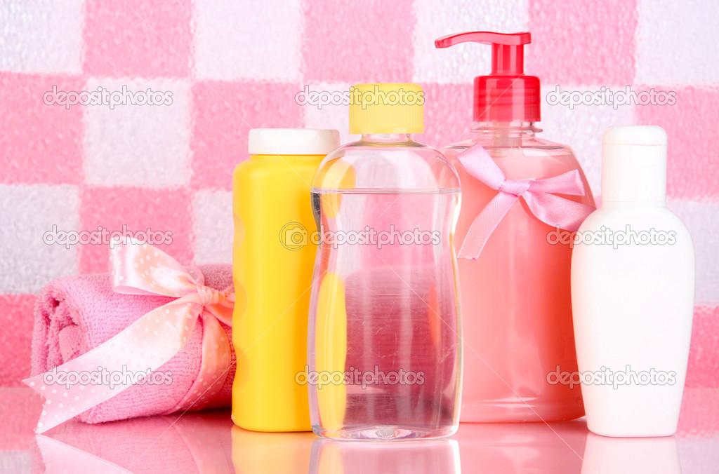 Cosmesi bambino e asciugamano in bagno su sfondo muro piastrelle