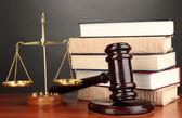 dřevěné kladívko, zlaté váhy spravedlnosti a knih o šedé pozadí