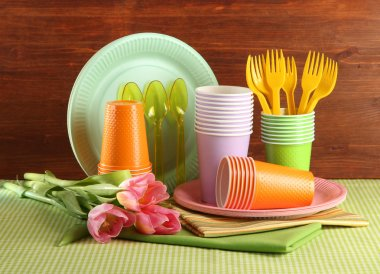 Multicolored plastic tableware on table with tulips on wooden background