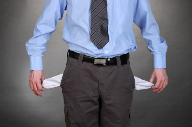 Business man showing his empty pockets, on grey background