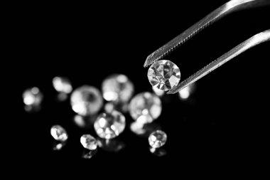 Beautiful shining crystal (diamond) in the tweezers, on black background