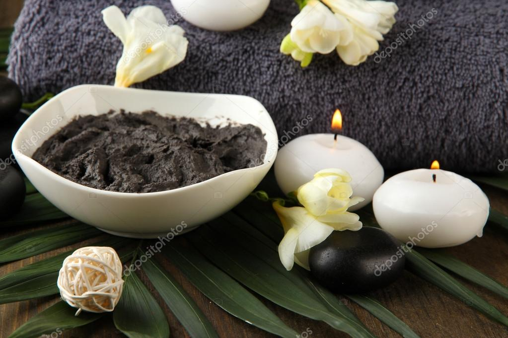 Composition with cosmetic clay for spa treatments, on wooden background