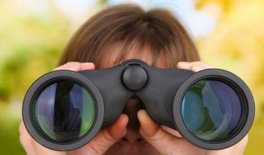 Black modern binoculars in hands on green background