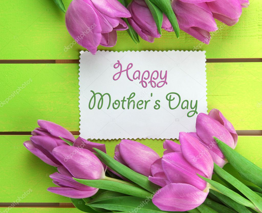 Beautiful bouquet of purple tulips and card on green wooden background