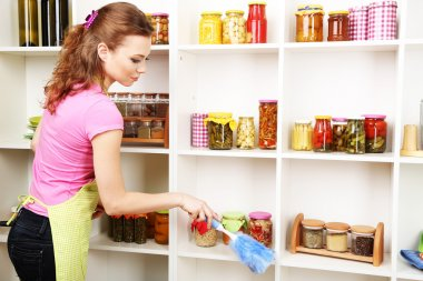 Young housewife cleaning up kitchen on grey background