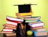 Könyvek és ellen a fából készült asztal zöld háttér iskolaszék magister sapka