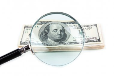 Hundred dollar bill and magnifying glass isolated on white