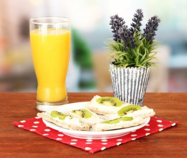 Tasty canapes with cheese and kiwi, on color plate, on bright background