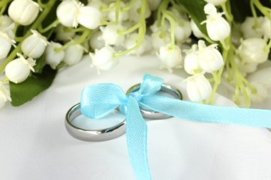 Wedding rings tied with ribbon on light gentle background