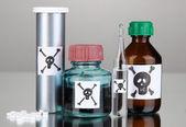 Tödliches Gift in Flaschen auf grauem Hintergrund