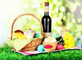 Photo Easter basket: Conceptual photo of traditional easter food in wicker basket, on green grass, on bright background