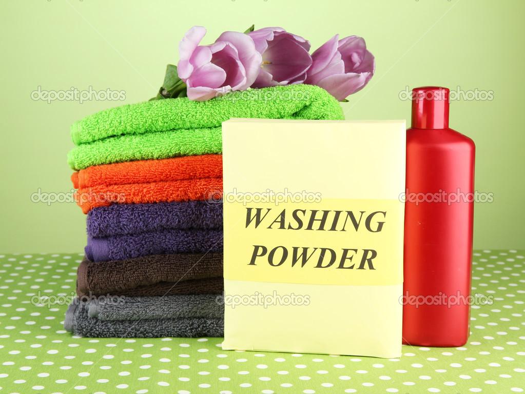 stapel van kleurrijke handdoeken, wassen poeder en fles conditioner