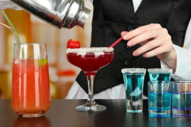 Barmen hand with shaker pouring cocktail into glass, on bright background