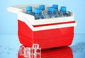 Utazás hűtőszekrény üveg víz és a jég-kocka, a kék háttér