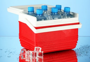 Traveling refrigerator with bottles of water and ice cubes, on blue background