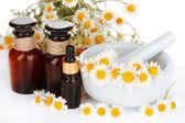 ätherisches Öl und Kamillenblüten in Mörtel hautnah