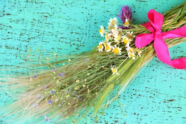 Bouquet of wild flowers and herbs, on color wooden background