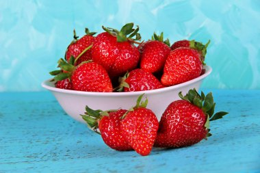 Strawberries in plate on blue background