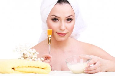 Beautiful young woman with cream for face mask and towel on her head isolated on white