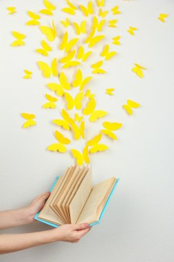 Paper yellow butterflies fly out of book